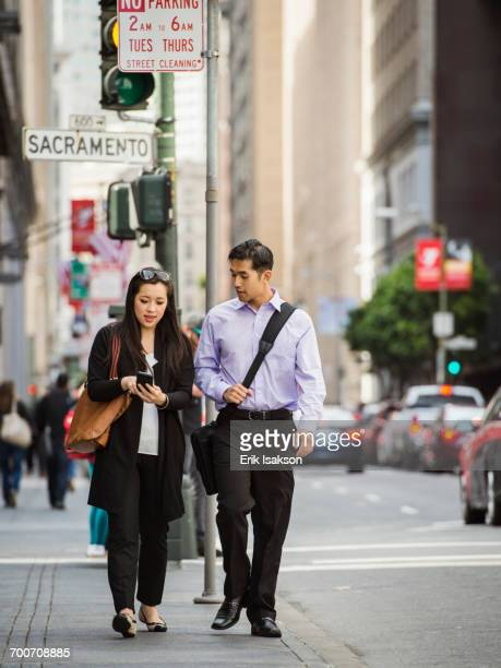 Chinese business people in city texting on cell phone