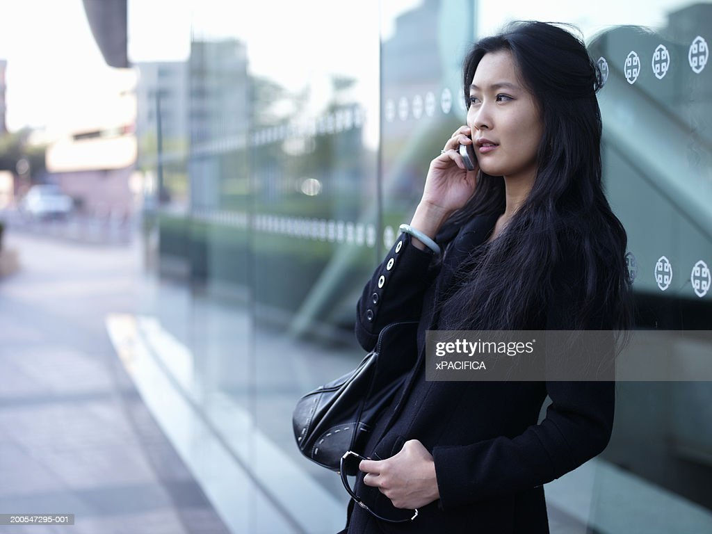 Chinese business woman using mobile phone outside office building : Stock Photo