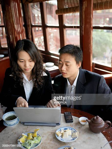 Chinese businessman and woman using laptop in traditional tea house