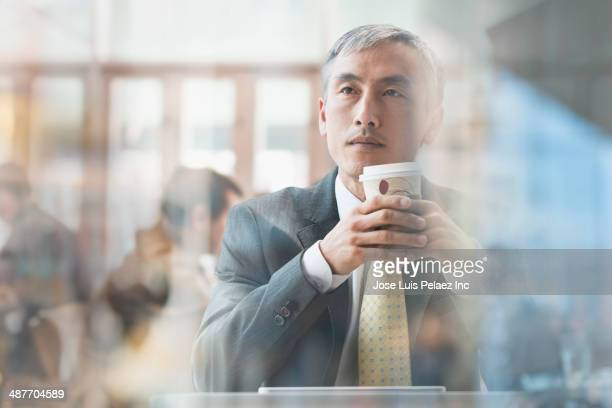 Chinese businessman drinking cup of coffee