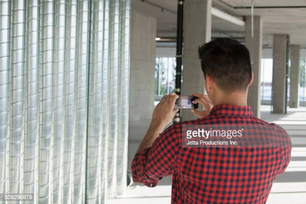 Chinese businessman photographing metal wall