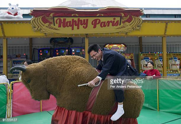 Chinese businessman rides a mechanical bull at a carnival stand at Windows Of the World Theme park on December 29 2008 in central Shenzhen China The...