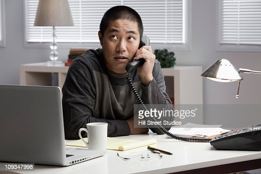 Chinese businessman talking on telephone at desk : Stock Photo