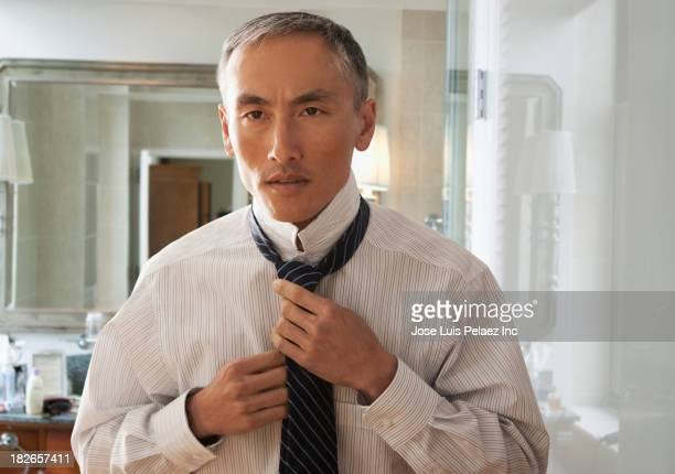 Chinese businessman tying his tie