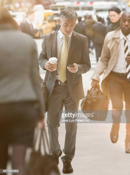 Chinese businessman using cell phone on city street