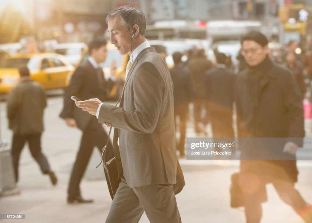 Chinese businessman using cell phone on city street : Stock Photo