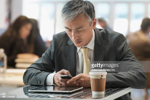 Chinese businessman using digital tablet in cafe