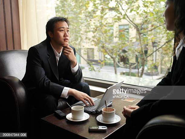 Chinese businessman using laptop with woman in cafe