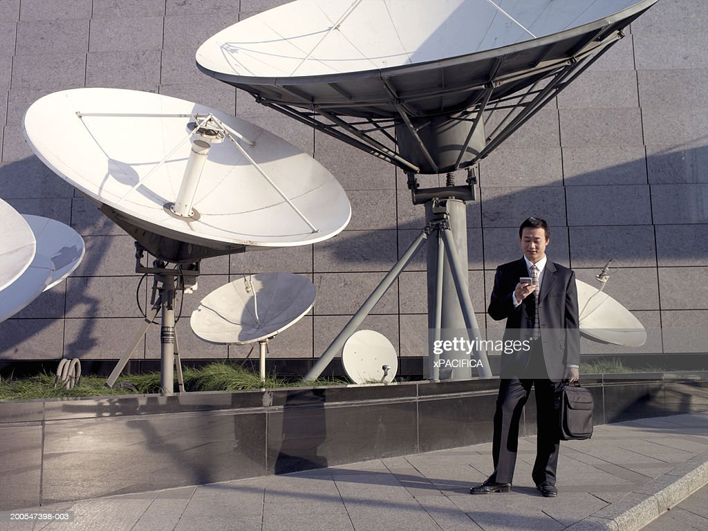 Chinese businessman using mobile phone by satellite dishes : Stock Photo