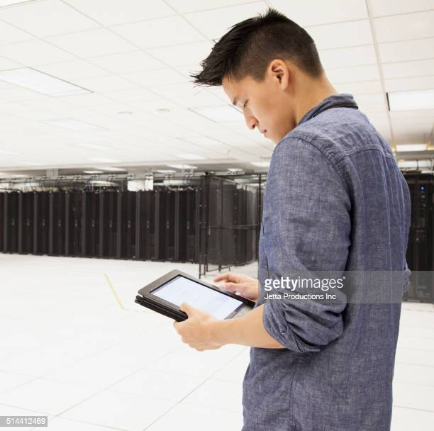 Chinese businessman using tablet computer in server room