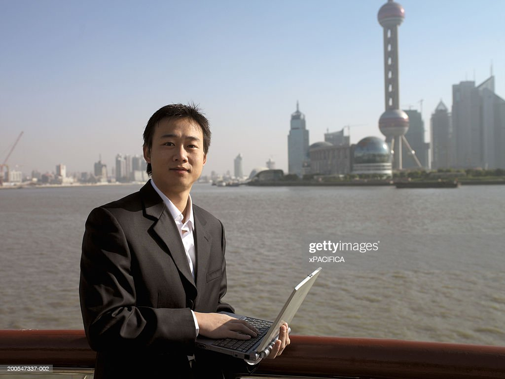Chinese businessman with laptop, against Pudong skyline, portrait : Stock Photo