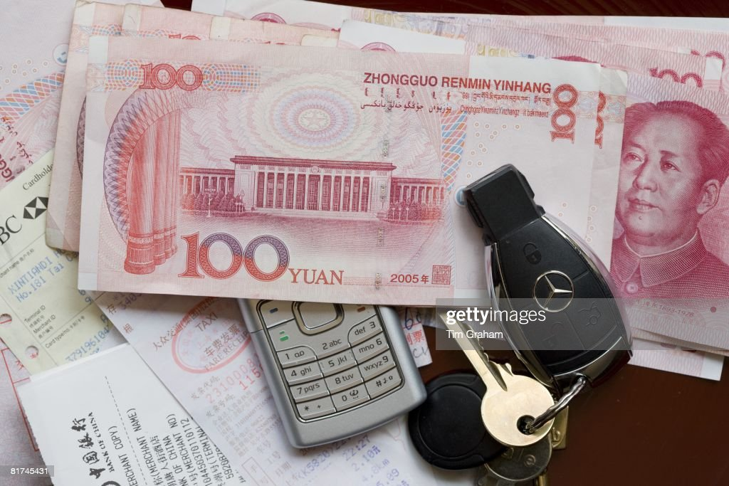 Chinese businessman's currency, one hundred Yuan bills, and receipts with Mercedes car key and mobile phone
