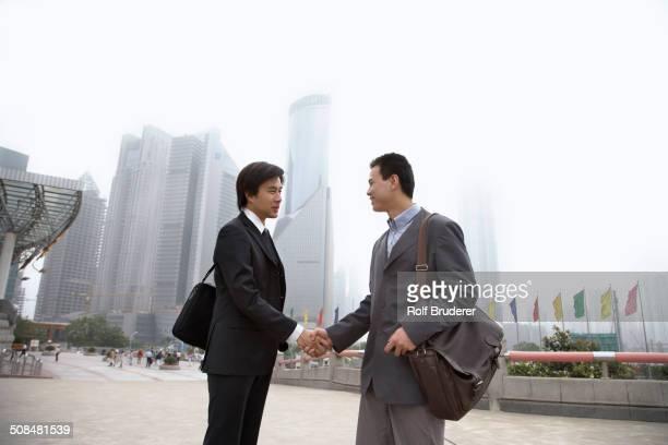 Chinese businessmen shaking hands, Shanghai, China