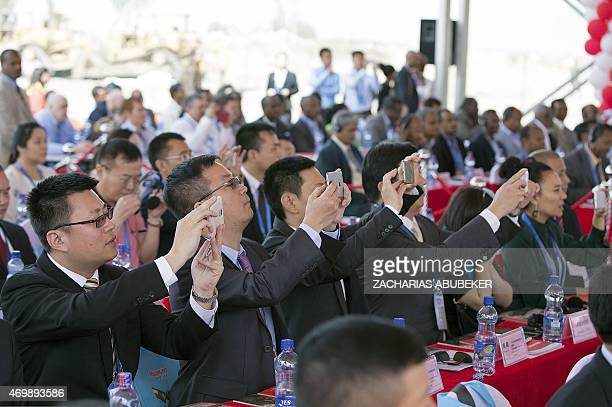 Chinese businessmen take pictures with their cell phones during the opening ceremony for the groundbreaking of the EthiopiaChina Dong Guan Huajian...