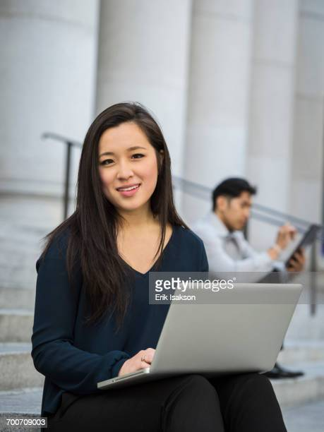 Chinese businesswoman sitting on staircase using laptop