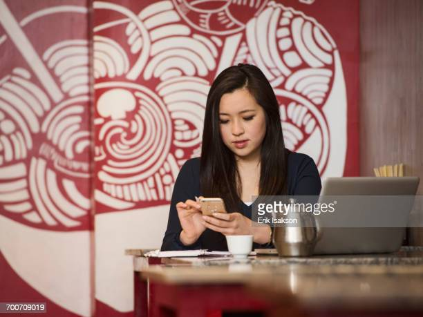 Chinese businesswoman texting on cell phone in restaurant