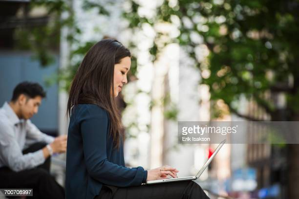 Chinese businesswoman typing on laptop in city
