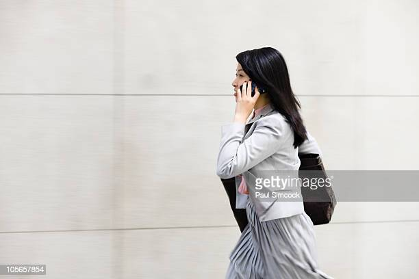 Chinese businesswoman walking and talking on cell phone