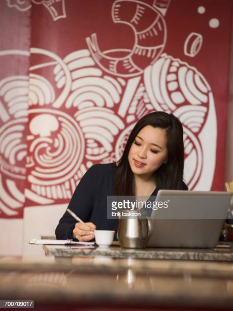 Chinese businesswoman writing in notebook in restaurant