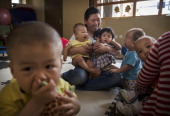 Chinese care worker holds orphaned children at a foster care center on April 2 2014 in Beijing China China's orphanages and foster homes used to be...