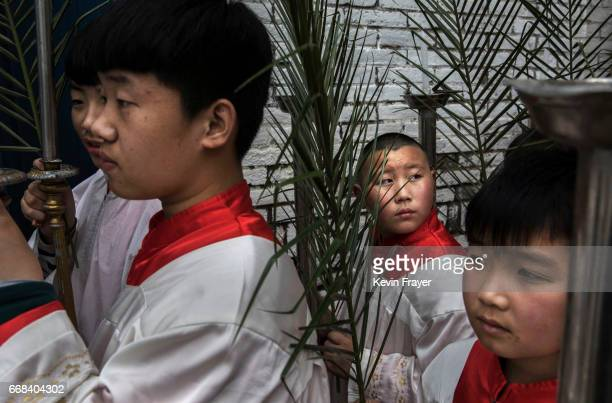 Chinese Catholic altar boys carry palm fronds as they take part in a procession at Palm Sunday Mass during the Easter Holy Week at an 'underground'...