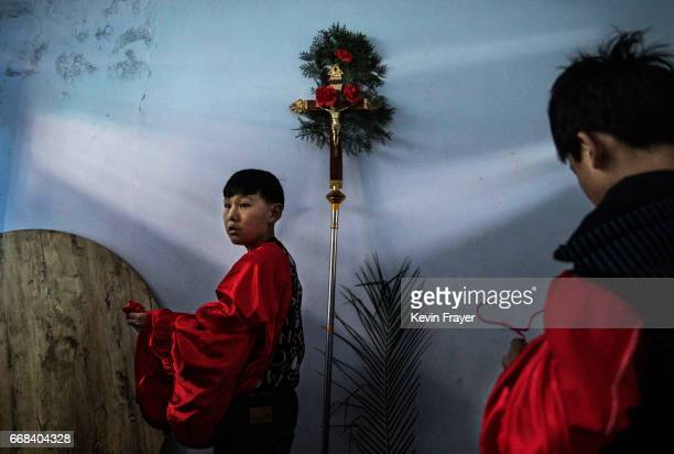 Chinese Catholic altar boys prepare before a procession for the Palm Sunday Mass during the Easter Holy Week at an 'underground' or 'unofficial'...