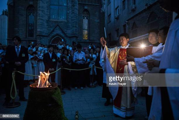 Chinese Catholic Bishop Zhang Hong blesses the flame used to light the Paschal Candle at a mass on Holy Saturday during Easter celebrations at the...