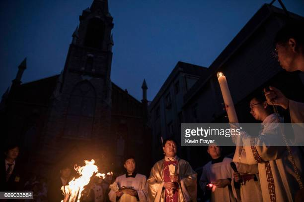 Chinese Catholic Bishop Zhang Hong centre second from left leads the lighting of the Paschal Candle at a mass on Holy Saturday during Easter...