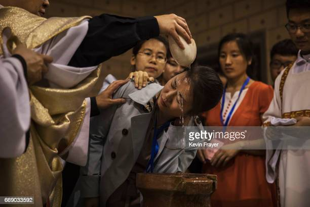 Chinese Catholic Bishop Zhang Hong left pours holy water on the head of a worshipper during a special baptism ceremony at a mass on Holy Saturday...