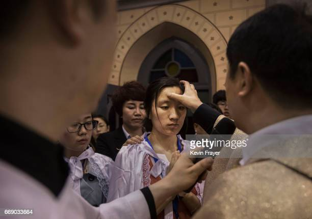 Chinese Catholic Bishop Zhang Hong right blesses newly baptized worshippers during a special ceremony at a mass on Holy Saturday during Easter...