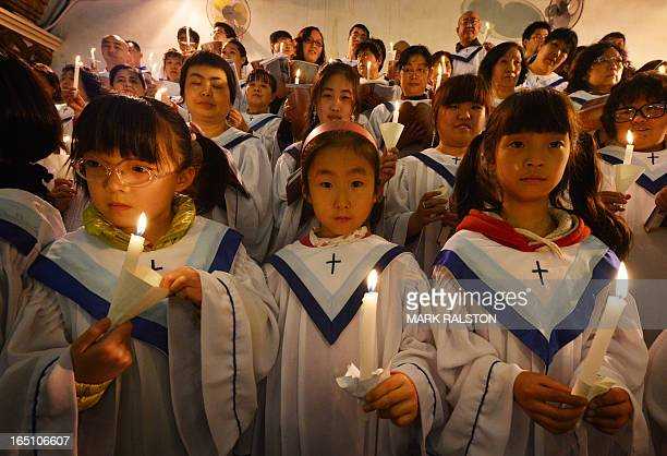 Chinese Catholic choir girls hold candles during an Easter service at the Cathedral of the Immaculate Conception in Beijing on March 30 2013 Experts...