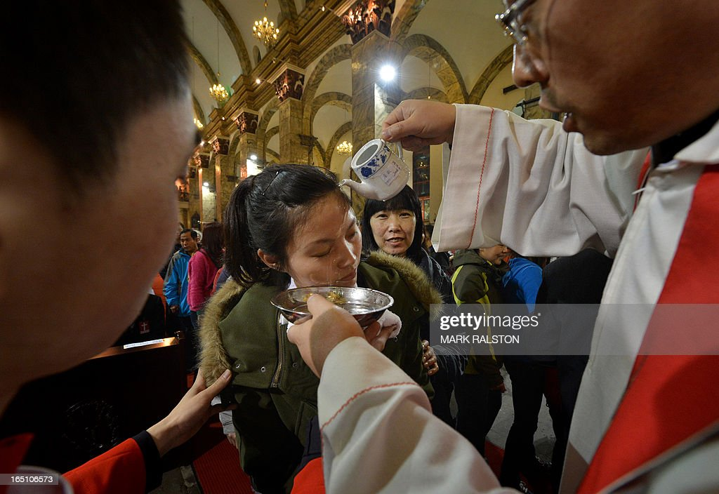 A Chinese Catholic is baptized during an Easter service at the Cathedral of the Immaculate Conception in Beijing on March 30, 2013. Experts estimate that there are as many as 12 million Catholics in China, with about half in congregations under the officially-administered Chinese Catholic Patriotic Association. The rest belong to non-sanctioned or so-called underground churches. AFP PHOTO/Mark RALSTON