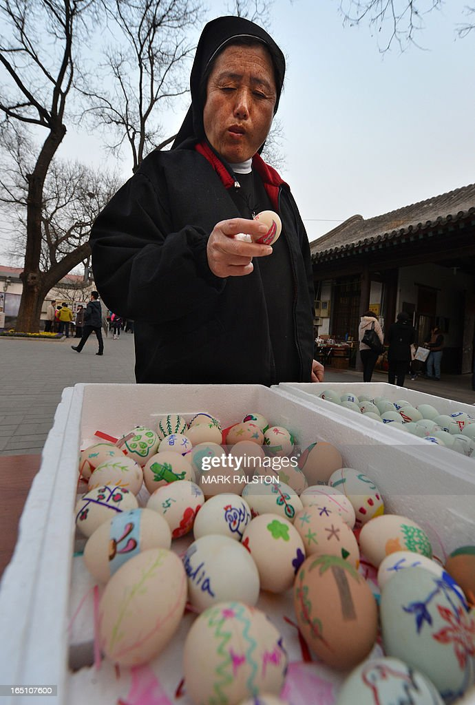 A Chinese Catholic nun checks an egg before an Easter service at the Cathedral of the Immaculate Conception in Beijing on March 30, 2013. Experts estimate that there are as many as 12 million Catholics in China, with about half in congregations under the officially-administered Chinese Catholic Patriotic Association. The rest belong to non-sanctioned or so-called underground churches. AFP PHOTO/Mark RALSTON