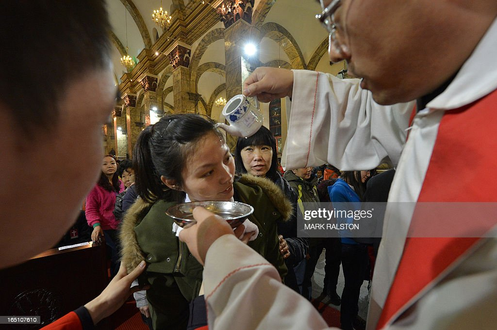 A Chinese Catholic woman is baptized during an Easter service at the Cathedral of the Immaculate Conception in Beijing on March 30, 2013. Experts estimate that there are as many as 12 million Catholics in China, with about half in congregations under the officially-administered Chinese Catholic Patriotic Association. The rest belong to non-sanctioned or so-called underground churches. AFP PHOTO/Mark RALSTON