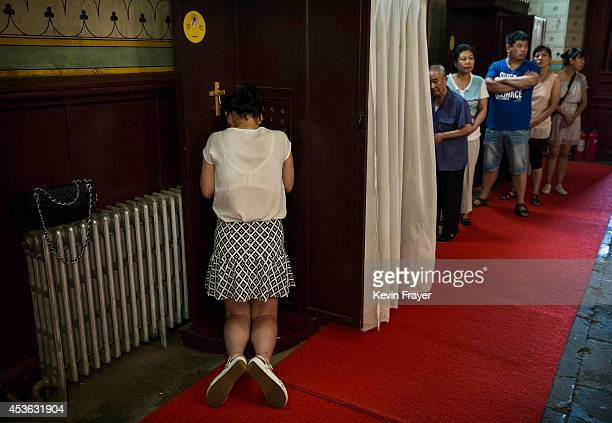 Chinese Catholic woman kneels at a confession booth during a service for the Assumption of the Virgin Mary at a government sanctioned church on...