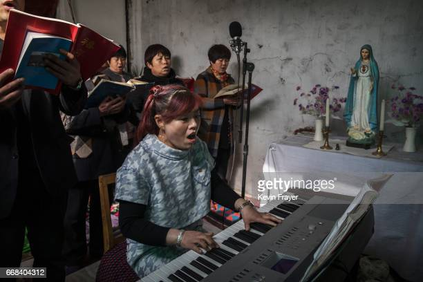 A Chinese Catholic woman plays a keyboard as she sings hymns at the Palm Sunday Mass during the Easter Holy Week at an 'underground' or 'unofficial'...