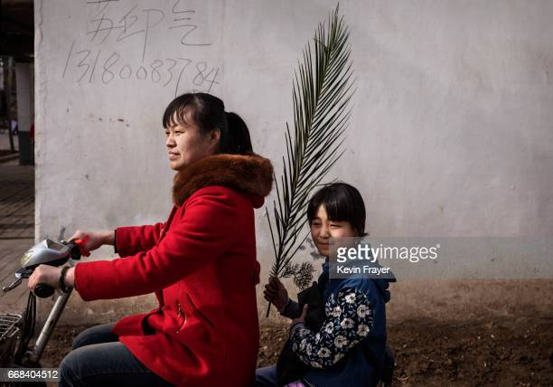 A Chinese Catholic worshipper and her daughter ride away with a palm frond after the Palm Sunday Mass during the Easter Holy Week at an 'underground'...