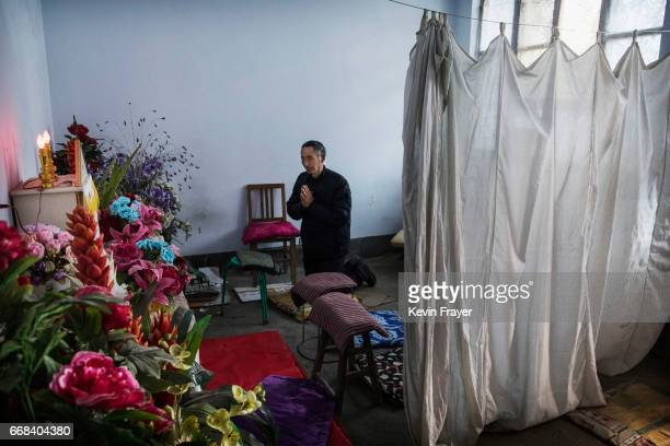 A Chinese Catholic worshipper kneels to pray following Palm Sunday Mass during the Easter Holy Week at an 'underground' or 'unofficial' church on...