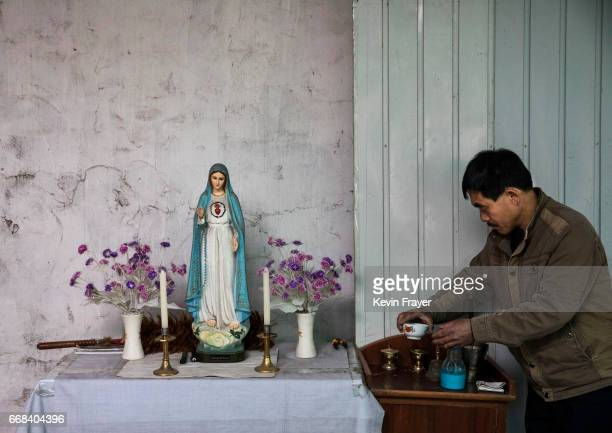 A Chinese Catholic worshipper prepares the communion tray before the Palm Sunday Mass during the Easter Holy Week at an 'underground' or 'unofficial'...