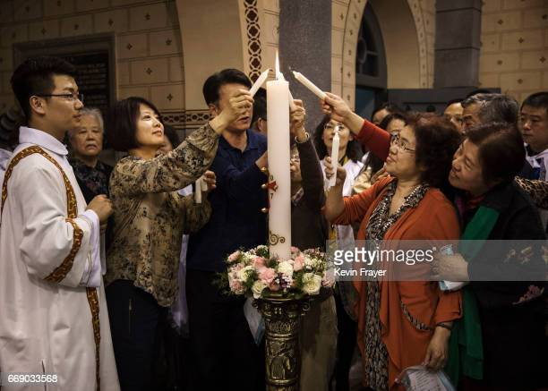 Chinese Catholic worshippers and clergy light candles during a special baptism ceremony at a mass on Holy Saturday during Easter celebrations at the...