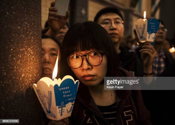 Chinese Catholic worshippers hold candles as they watch during a special baptism ceremony at a mass on Holy Saturday during Easter celebrations at...