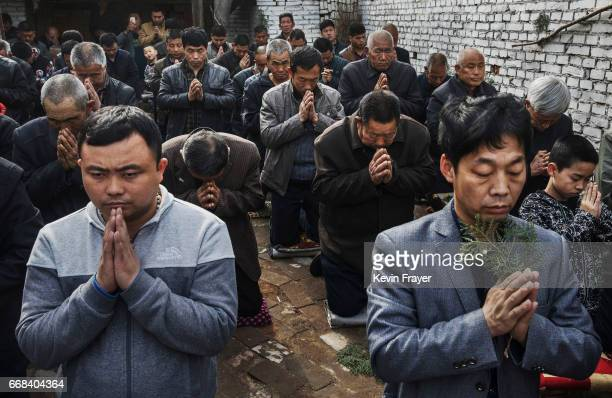 Chinese Catholic worshippers kneel and pray during Palm Sunday Mass during the Easter Holy Week at an 'underground' or 'unofficial' church on April 9...