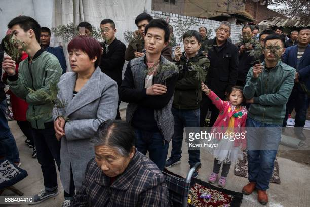 Chinese Catholic worshippers pray at a Palm Sunday Mass during the Easter Holy Week at an 'underground' or 'unofficial' church on April 9 2017 near...