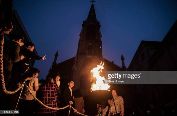 Chinese Catholics gather near the flame used to light the Paschal Candle at a mass on Holy Saturday during Easter celebrations at the government...