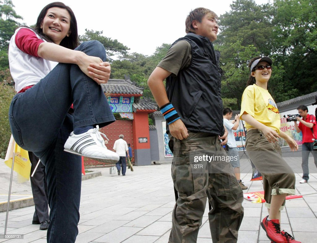 Chinese celebrities top model Jiang Peilin popular singer Sun Lan and actress Xie Na warm up before their climb up Fragrant Hills in Beijing 11 June...