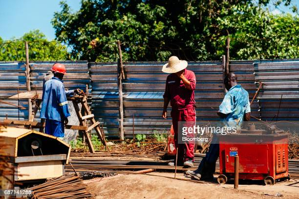 Chinese center and African workers work at the construction site for a hydro pumping station which will supply water from the Limpopo river to nearby...