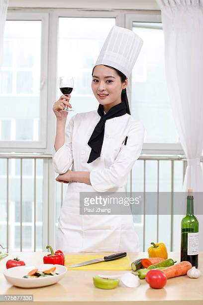 Chinese chef in the kitchen holding red wine