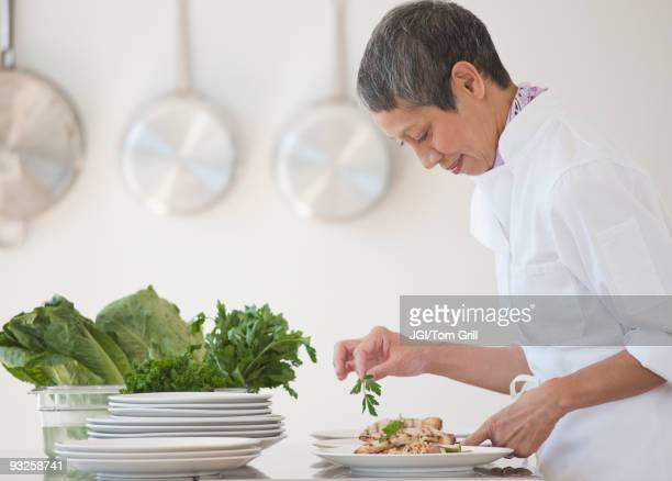 Chinese chef plating meals in professional kitchen