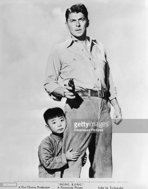 Chinese child actor Danny Chang clings to the leg of American actor and politician Ronald Reagan in a publicity still for the feature film 'Hong...