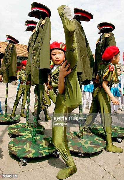 Chinese children dressed in replica military uniforms wait to perform a dance to mark International Children's Day on June 1 2005 in Beijing China